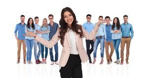 Smiling businesswoman leader shrugging in front of the team. With palms pointing up while standing on white background royalty free stock photography