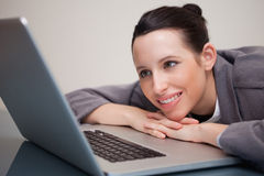 Smiling businesswoman leaning against her laptop Royalty Free Stock Photos