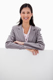 Smiling businesswoman leaning on blank wall Stock Images
