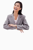 Smiling businesswoman leaning on a blank wall Royalty Free Stock Image
