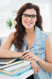 Smiling businesswoman leaning on notebooks Stock Images