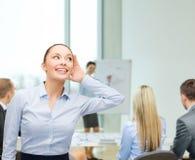 Smiling businesswoman listening gossig Royalty Free Stock Image