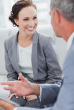 Smiling businesswoman listening to her workmate talking Stock Photos