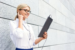 Smiling businesswoman listening to music Stock Photos
