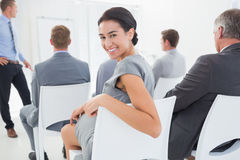 Smiling businesswoman looking at camera during conference Royalty Free Stock Images