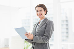 Smiling businesswoman looking at camera and using her tablet Royalty Free Stock Photos