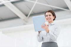 Smiling businesswoman looking at camera and using her tablet Royalty Free Stock Photo