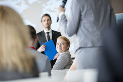 Smiling businesswoman looking colleague speaking during seminar.  royalty free stock photo