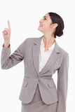 Smiling businesswoman looking and pointing up Stock Photography