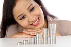 Smiling businesswoman looking at stack of coins - Money growth Stock Photos