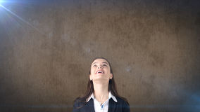 Smiling businesswoman looking up at copyspace. Standing over brown background. Royalty Free Stock Image