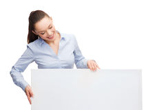 Smiling businesswoman lookint at white blank board Royalty Free Stock Photo