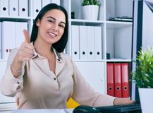 Happy woman giving thumbs up success sign sitting at computer PC with smiling face. Smiling businesswoman looks in camera sitting at workplace. White collar Stock Photo