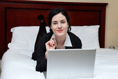 Smiling Businesswoman Lying on Bed With Laptop Royalty Free Stock Photos