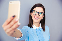 Smiling businesswoman making selfie photo. On smartphone. Wearing in blue shirt and glasses. Standing over gray background royalty free stock photography