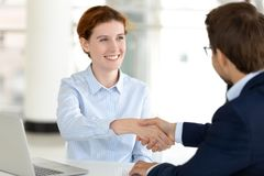 Smiling businesswoman manager broker handshaking businessman client at meeting. Smiling businesswoman manager broker handshaking businessman client customer at royalty free stock image