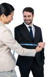 Smiling businesswoman measuring businessman sleeve Royalty Free Stock Image