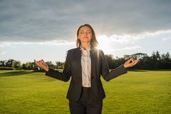 Smiling businesswoman meditating in park. Portrait of smiling businesswoman meditating in park Royalty Free Stock Photo