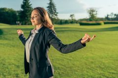 Smiling businesswoman meditating in park. Portrait of smiling businesswoman meditating in park Royalty Free Stock Photos
