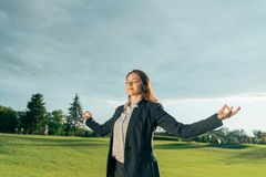 Smiling businesswoman meditating in park. Portrait of smiling businesswoman meditating in park Stock Images