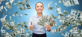 Smiling businesswoman with money showing thumbs up. Business, money, finance, people and banking concept - smiling businesswoman with heap of dollar cash money Royalty Free Stock Photos