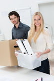 Smiling businesswoman moving into a new office. Assisted by a handsome male colleague as they carry across her files and possessions in boxes Stock Photo