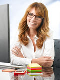 Smiling businesswoman at office desk with a computer Stock Image