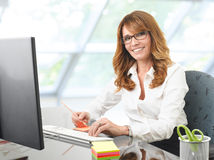 Smiling businesswoman at office desk with a computer Royalty Free Stock Photo