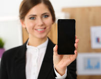 Smiling businesswoman in office hold cellphone in hands and show Royalty Free Stock Photos