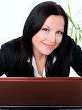 Smiling businesswoman in office with laptop Stock Images
