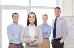 Smiling businesswoman in office with team on back Royalty Free Stock Photos
