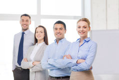 Smiling businesswoman in office with team on back Stock Image