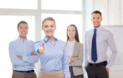 Smiling businesswoman in office with team on back Stock Photo