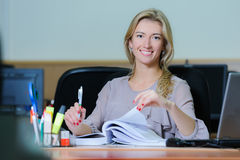 Smiling businesswoman in the office. Smiling young girl in the office sitting at a table flipping a book with a pen Stock Photo