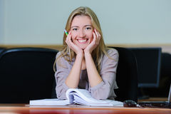 Smiling businesswoman in the office. Smiling young girl in the office sitting at a table with a pen and book Stock Photos