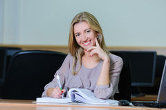 Smiling businesswoman in the office. Smiling young girl in the office sitting at a table with a pen and book Royalty Free Stock Images