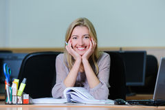 Smiling businesswoman in the office. Smiling young girl in the office sitting at a table with a pen and book Stock Image