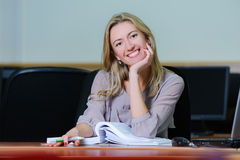 Smiling businesswoman in the office. Smiling young girl in the office sitting at a table with a pen and book Stock Photography