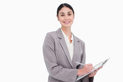 Smiling businesswoman with pen and clipboard. Against a white background Royalty Free Stock Photo