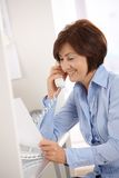 Smiling businesswoman on phone call reading paper. Royalty Free Stock Photos