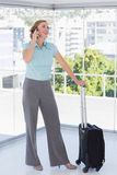 Smiling businesswoman on the phone leaning on suitcase. Standing in office Stock Image