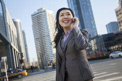 Smiling businesswoman on the phone and looking away in the street in Beijing Stock Photos