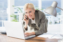 Smiling businesswoman on the phone looking at camera Stock Photo