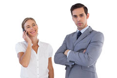 Smiling businesswoman on the phone next to her colleague. On white background Royalty Free Stock Photography