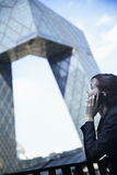 Smiling businesswoman on the phone outside in Beijing looking at the CCTV building Royalty Free Stock Photos