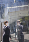 Smiling businesswoman on the phone outside in Beijing looking at her reflection in the glass of the building Royalty Free Stock Images