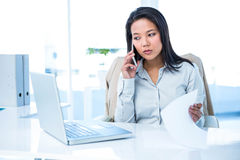 Smiling businesswoman on phone reading document Stock Photography