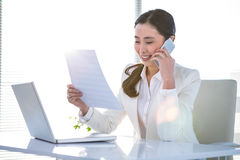 Smiling businesswoman on phone reading document Royalty Free Stock Image