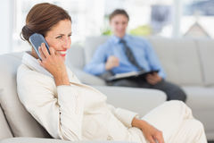 Smiling businesswoman on the phone sitting on couch Royalty Free Stock Image