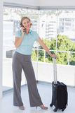 Smiling businesswoman on the phone with suitcase. Standing in office Stock Images